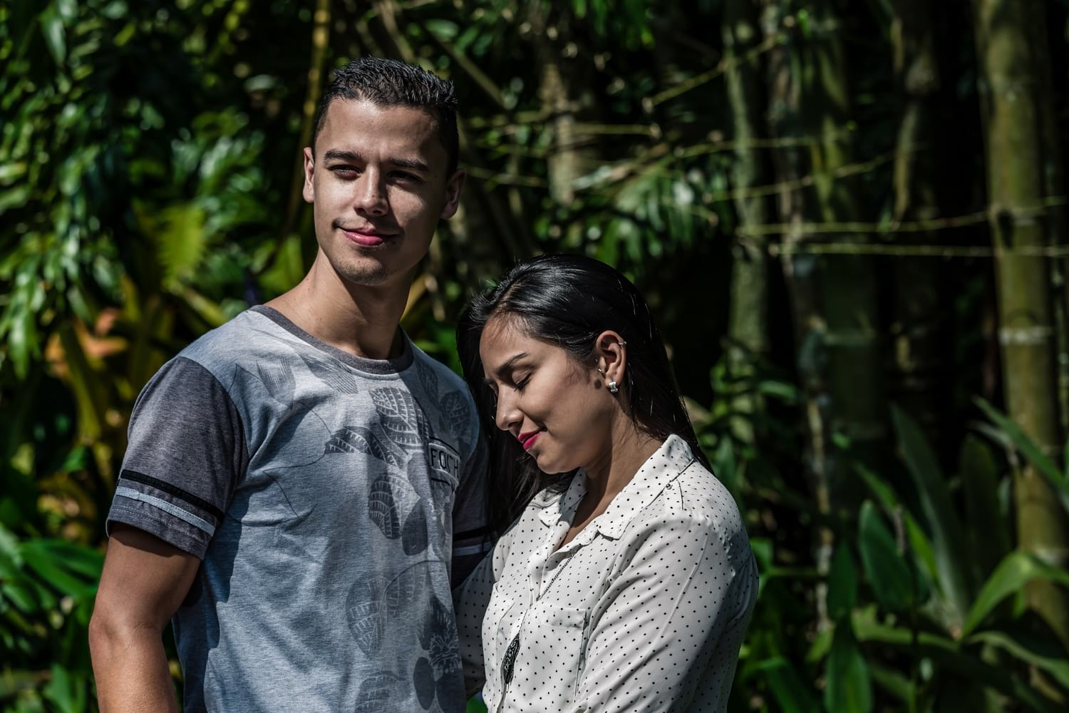 Young couple in Costa Rica botanical garden with their arms around each other for engagement picture.