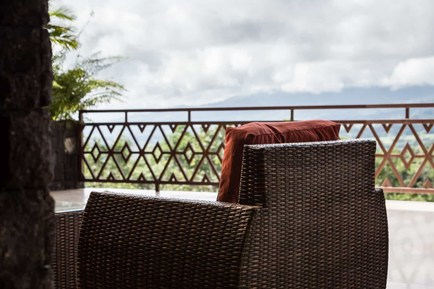 Side view of the terrace overlooking a rainforest and the Arenal Volcano.