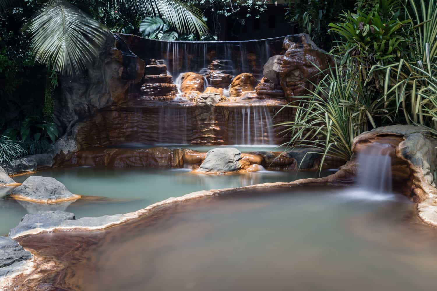 Thermal pool and waterfalls at Treetops open-air area for weddings at The Springs Resor, Arenal