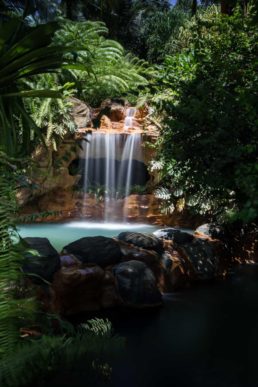 Waterfall feeding thermal pool by open-air wedding area at El Ranchito.