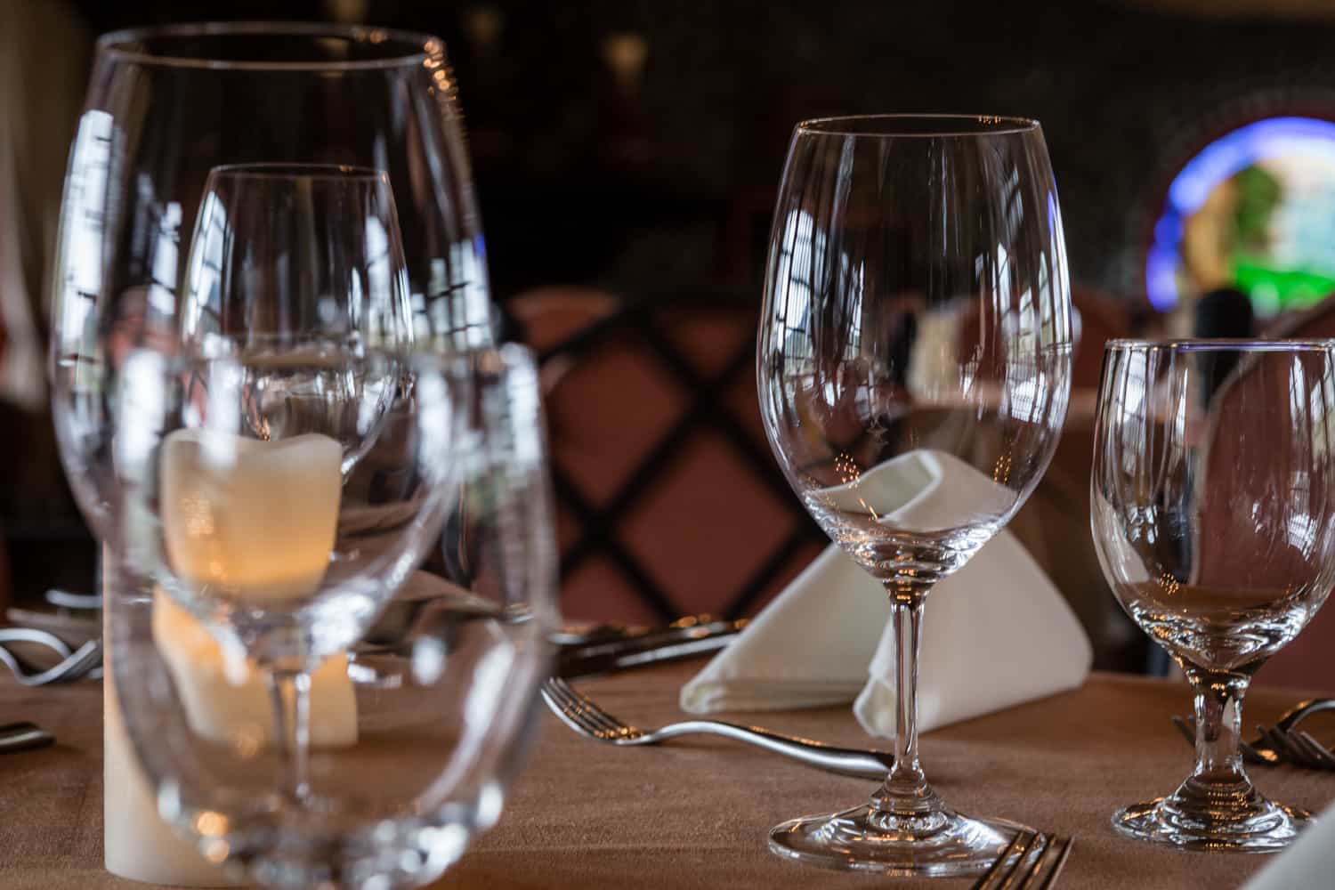 Close-up photo of wine glasses and table setting at Peace Lodge restaurant.