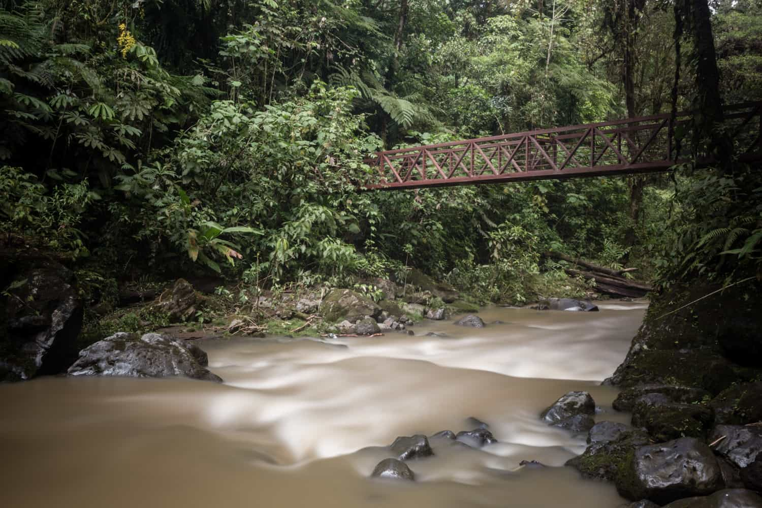 Long exposure photo of river flowing under bride ideal for post wedding ceremony photos.