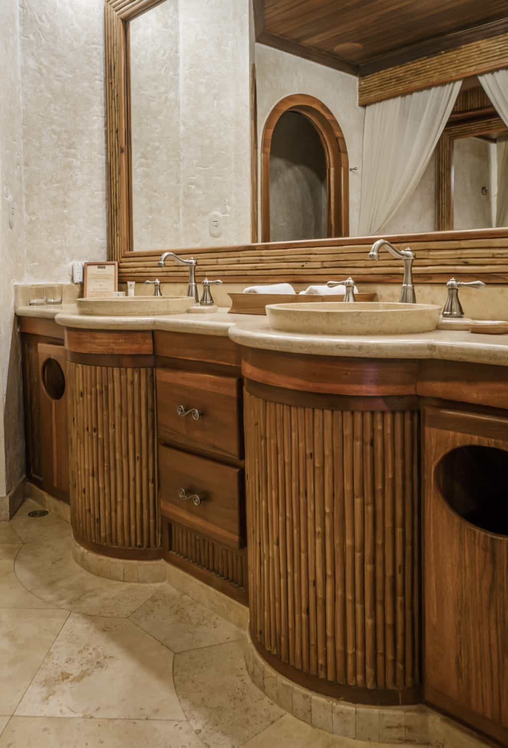 Bathroom vanity with natural stone counter and dual sinks with large mirror.