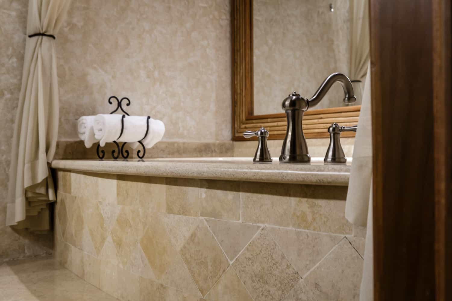 Side view of natural stone tile on guest room jacuzzi.