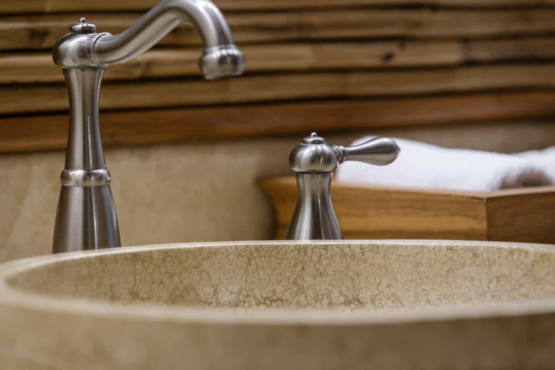 Closue-up of round stone sink on natural stone vanity.