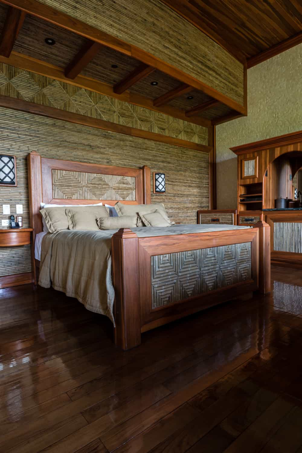 King bed in guest room with wood floors and ceilings.