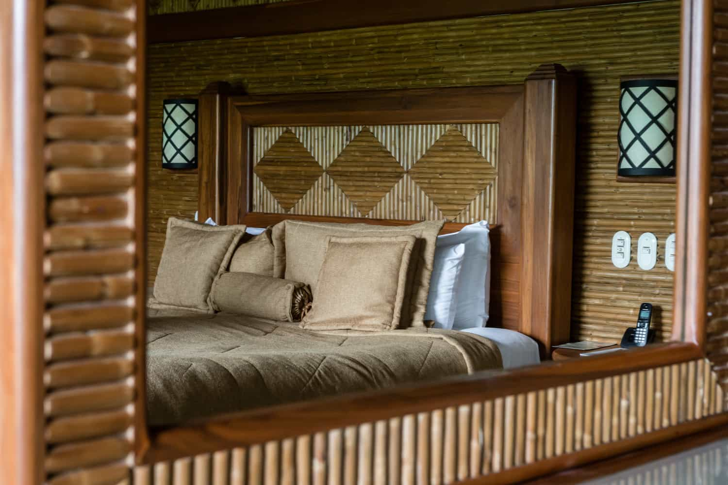 Reflection of king bed in mirror in deluxe guest room.