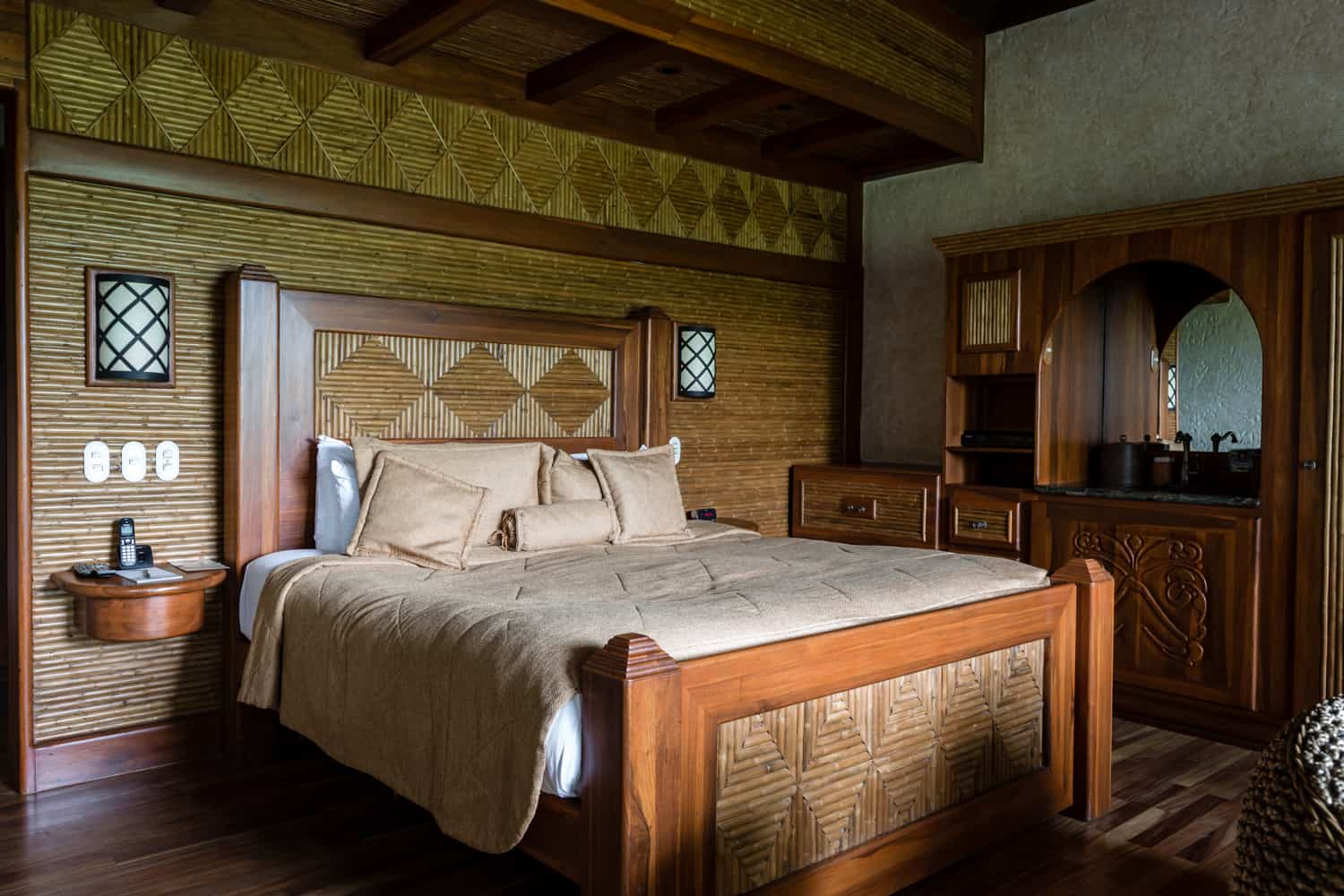 Guest room with wood king bed in middle of room.