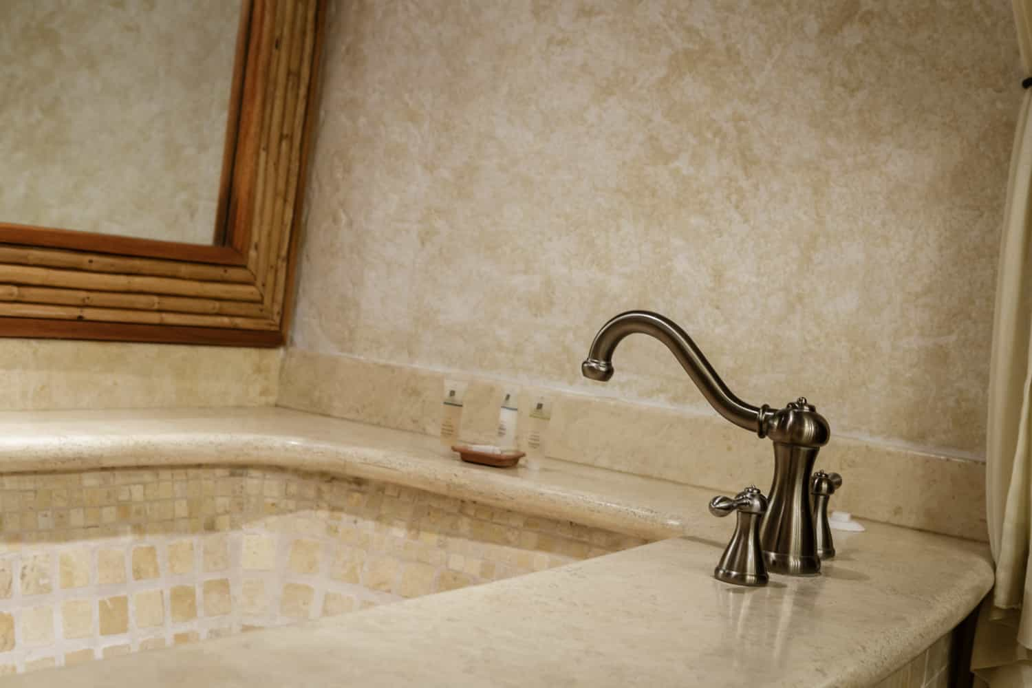 Natural stone jacuzzi tub in guest room bathroom.