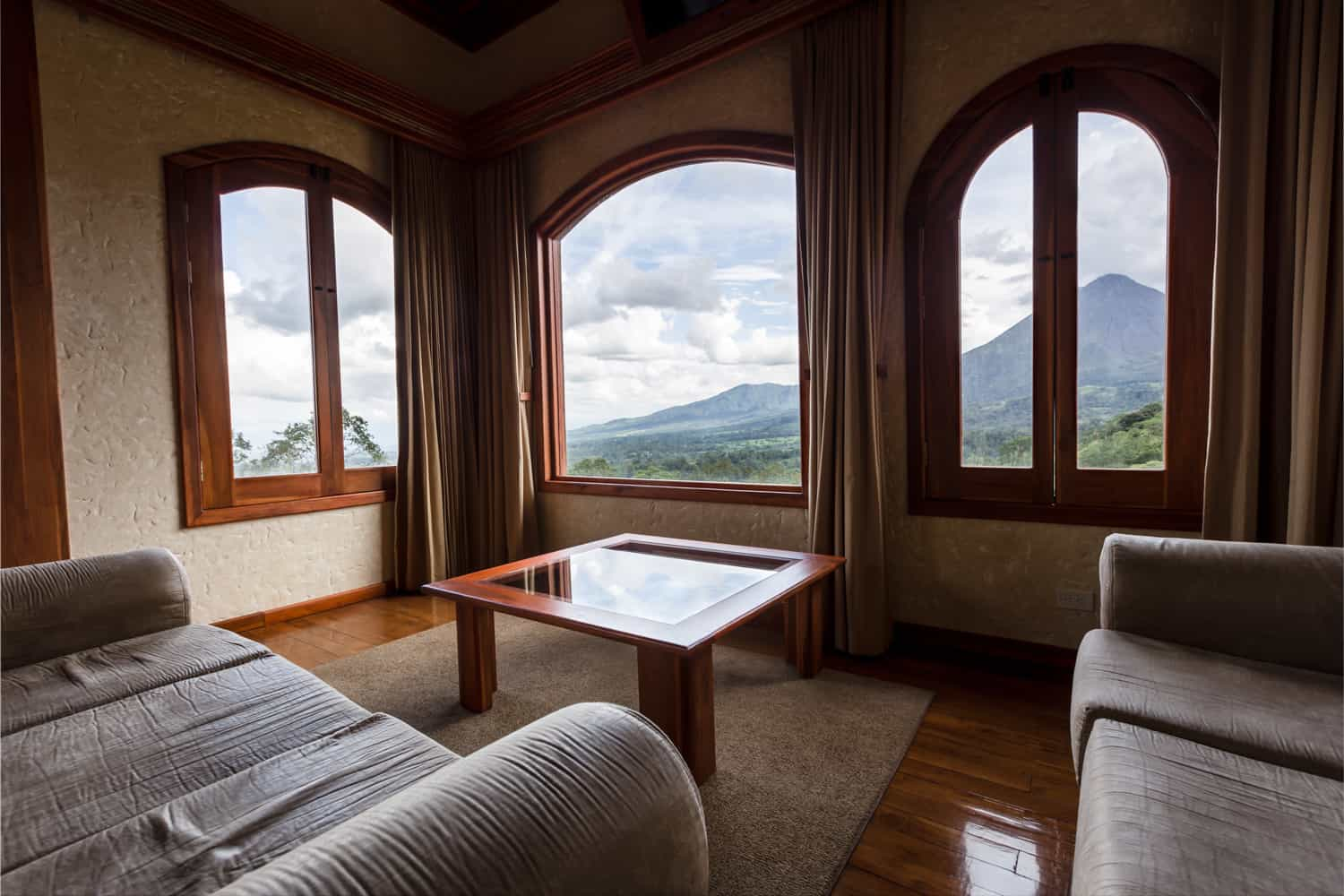 Arched windows in Spring Resort penthouse with view of rainforest.