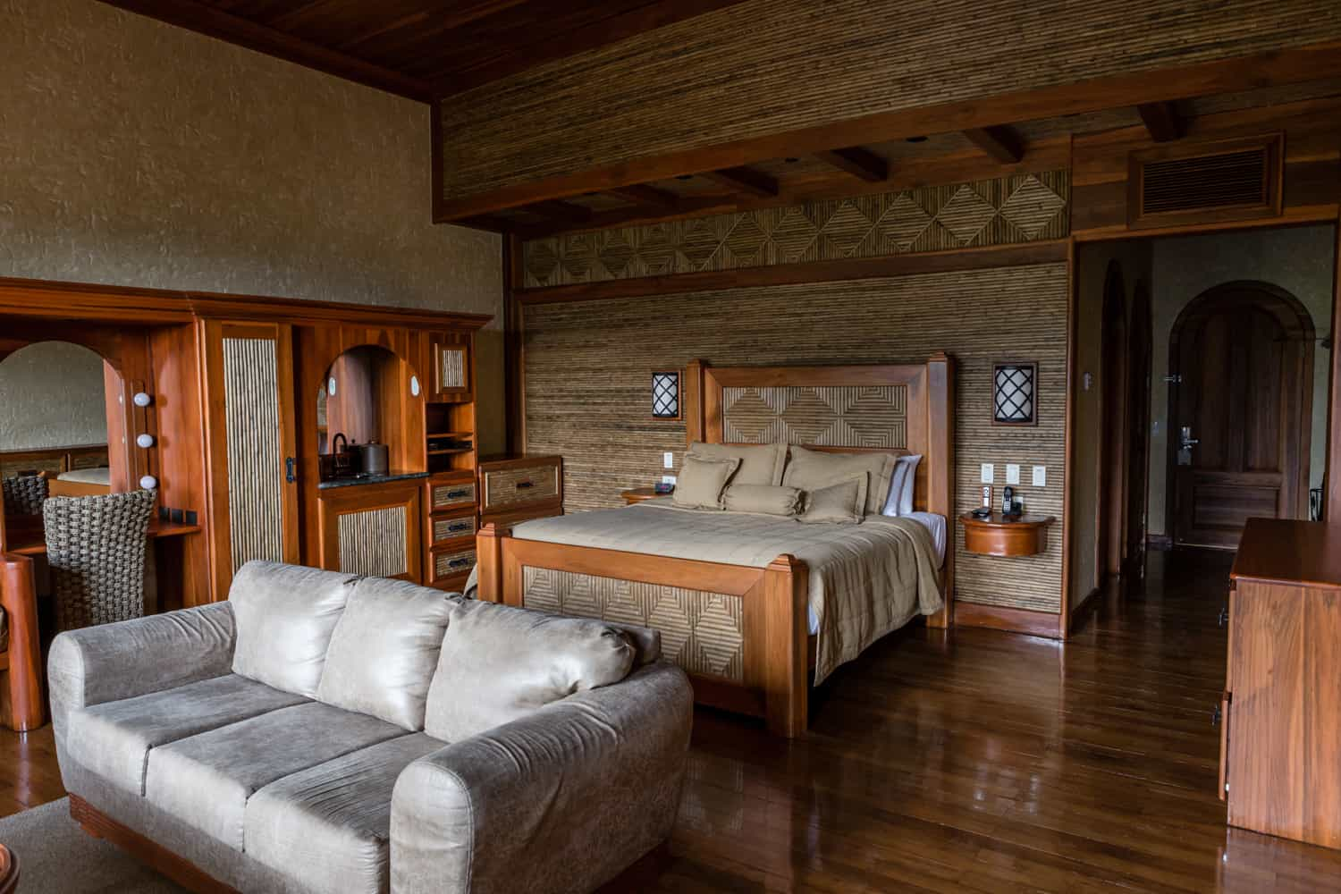 Master bedroom with king bed and wood floors.