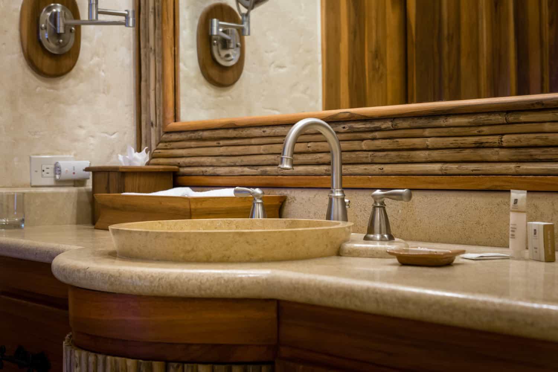 Vanity mirror in master bath with round stone sinks.