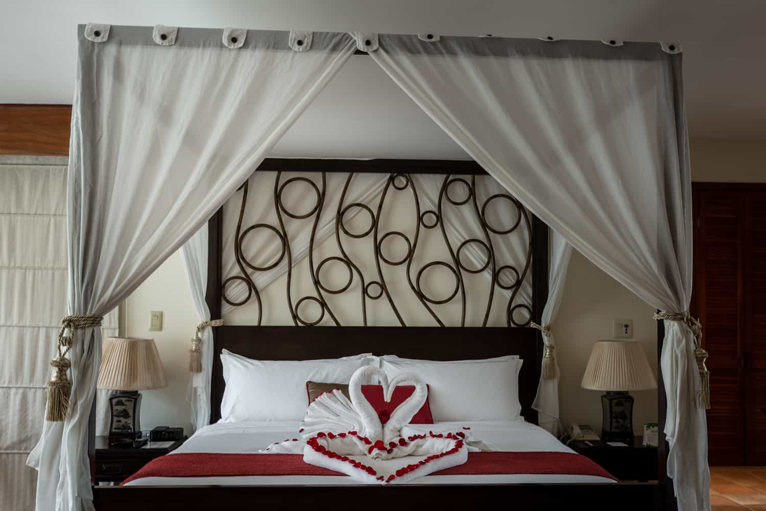 Towels folded into swans in front of heart of roses on canopy bed.