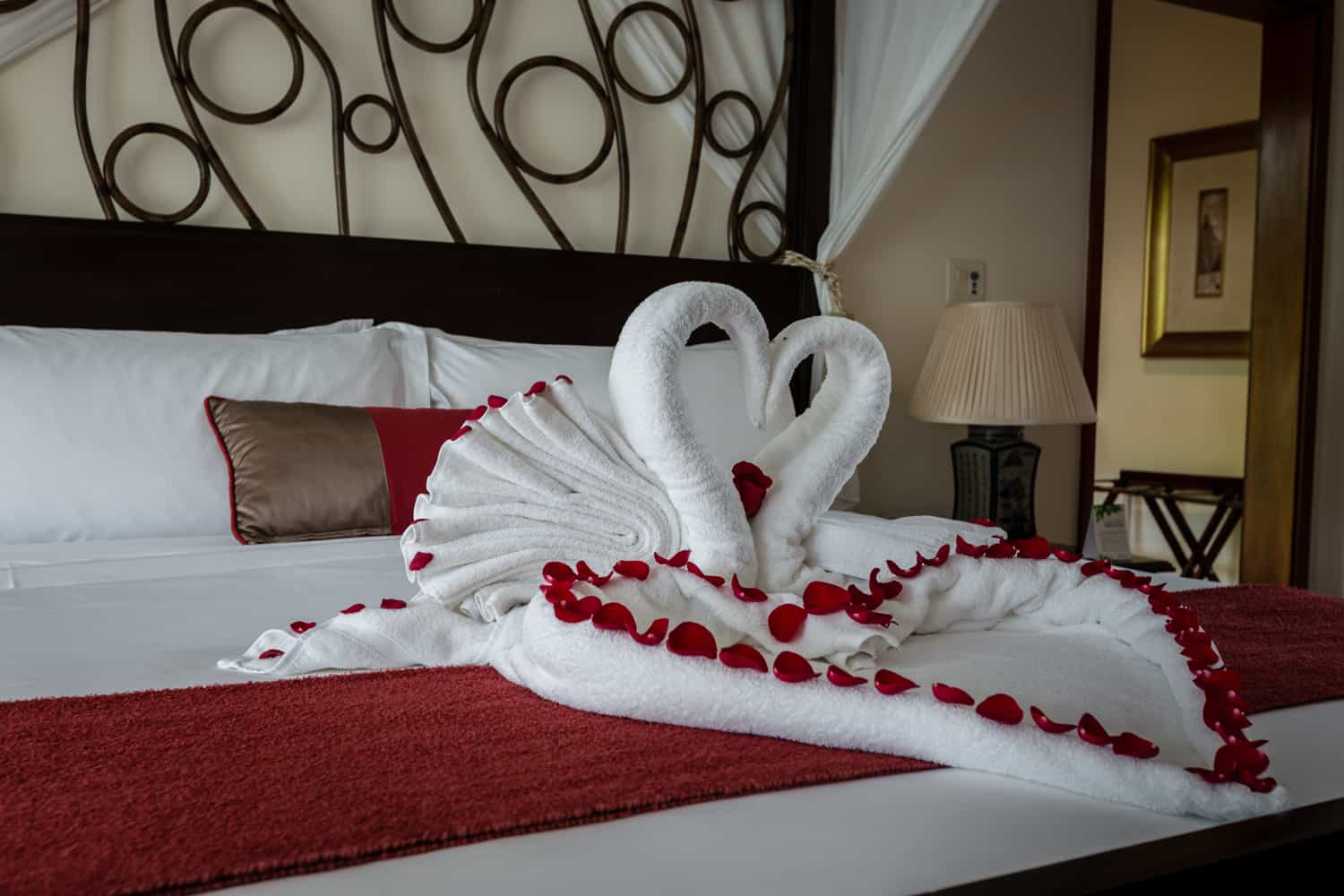 Swans made from towels kissing on honeymoon suite bed.