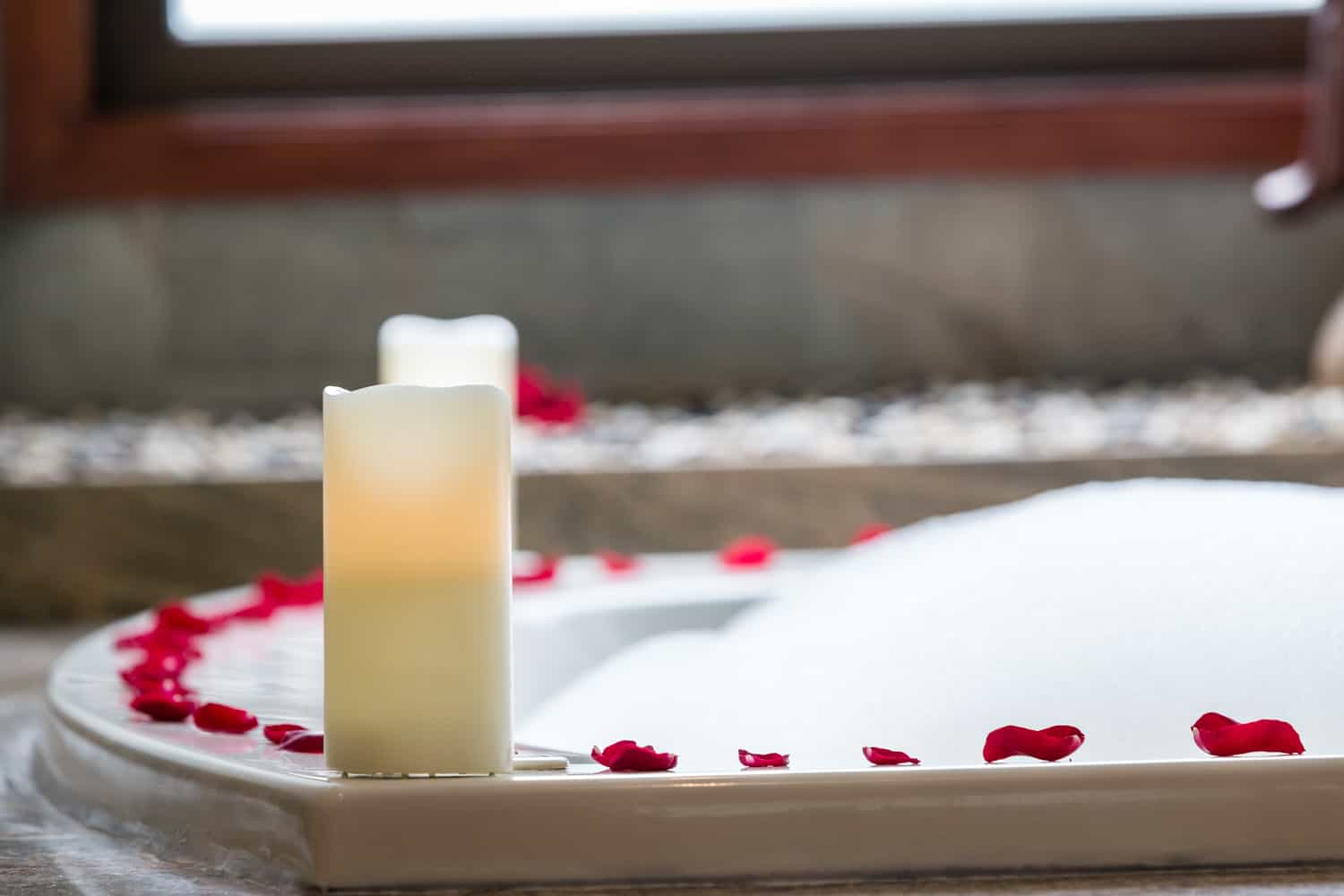 Red rose petals on jacuzzi tub for romantic couple's bath.