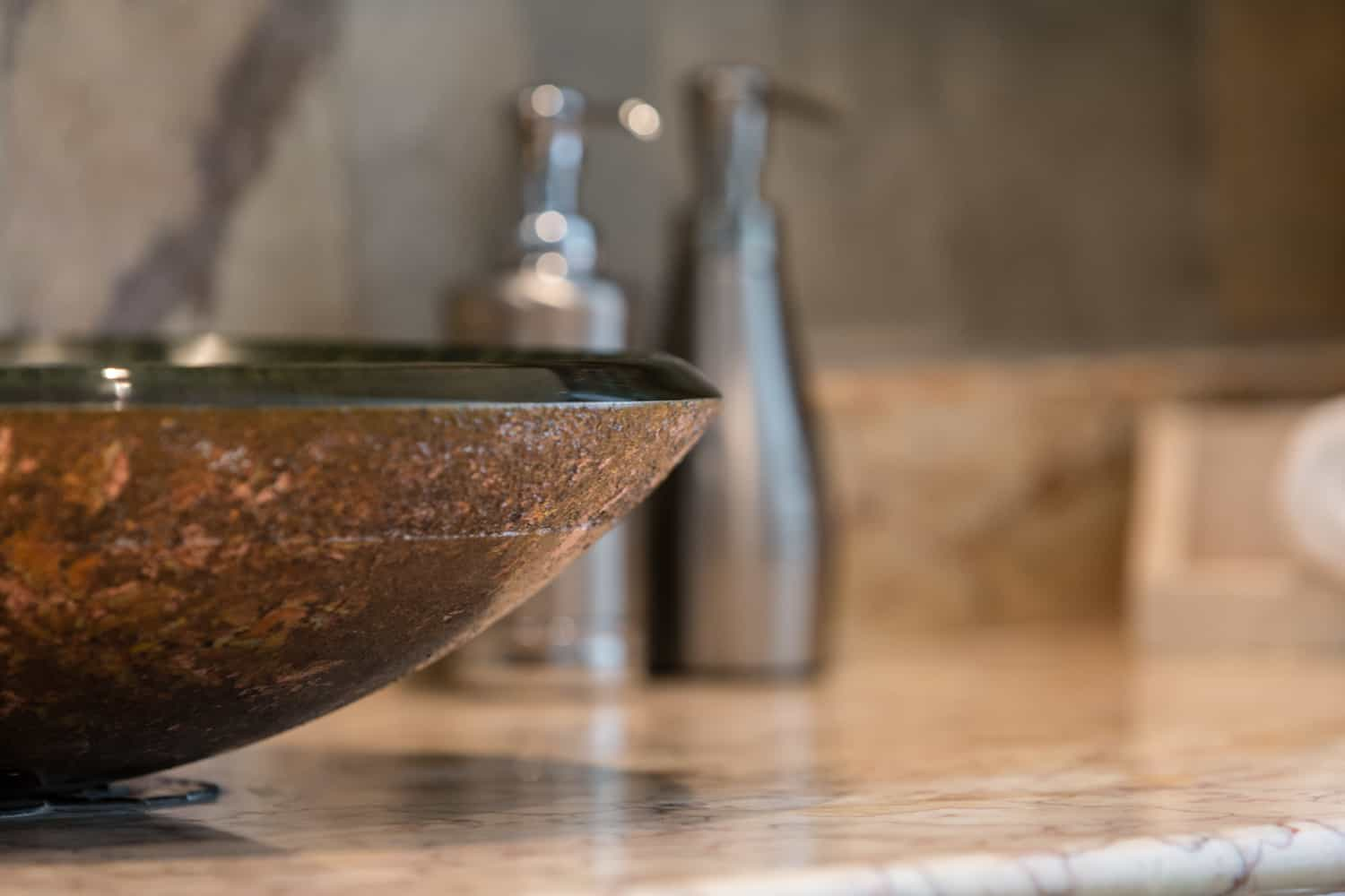 Ornate glass bowl sink on natural stone counter in bathroom.