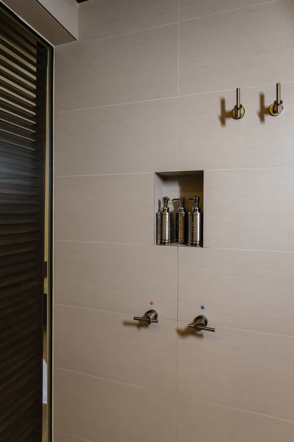 Shower niche and towel holders in beautiful guest room shower.