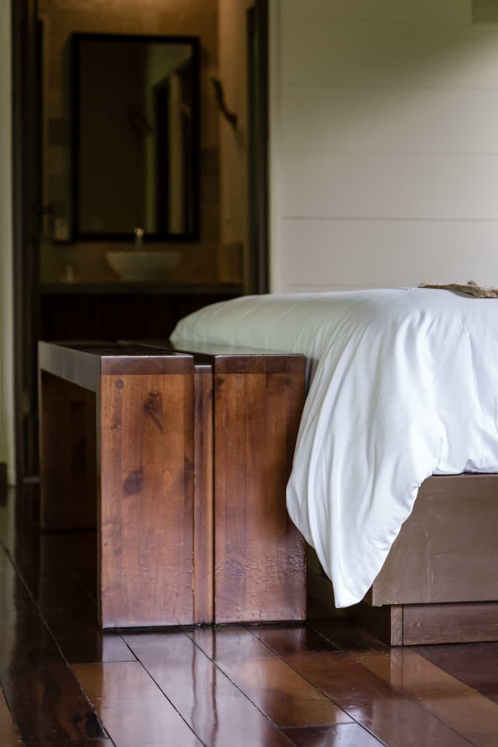 Beautiful wood floor and furniture in front of honeymoon bed.