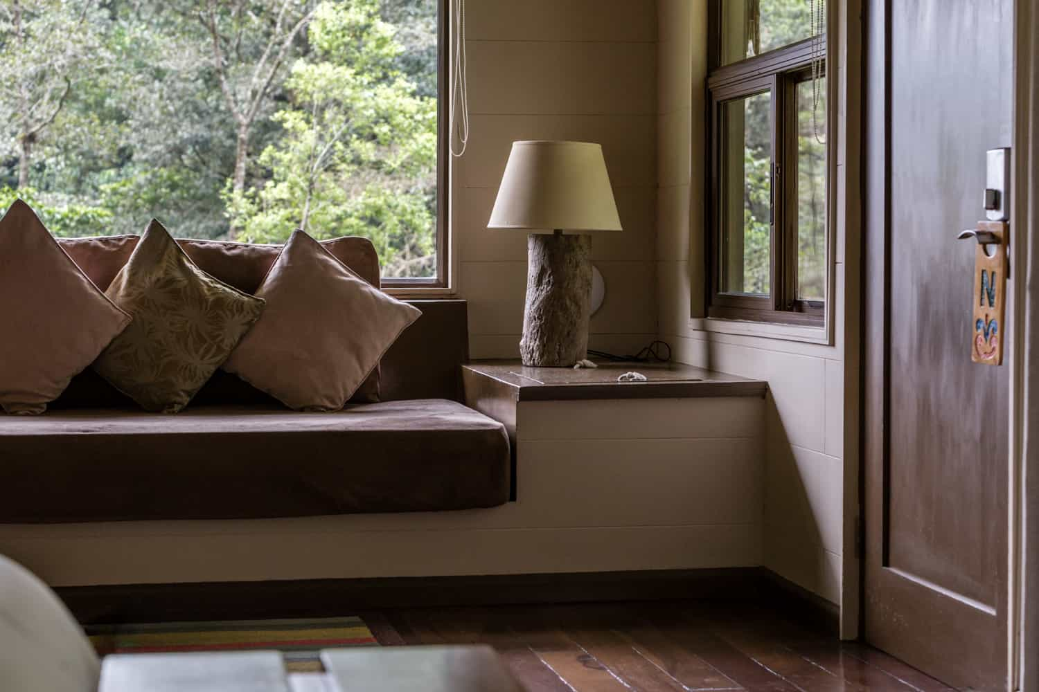 Couch by window with cloud forest view by suite entrance.