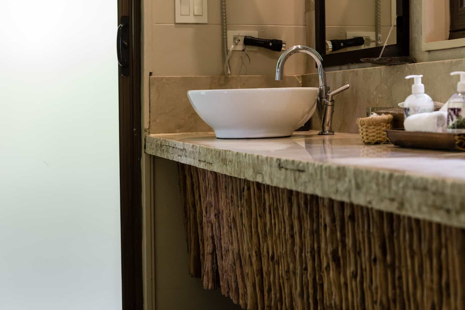 Lovely natural stone bathroom vanity with artful woodwork.