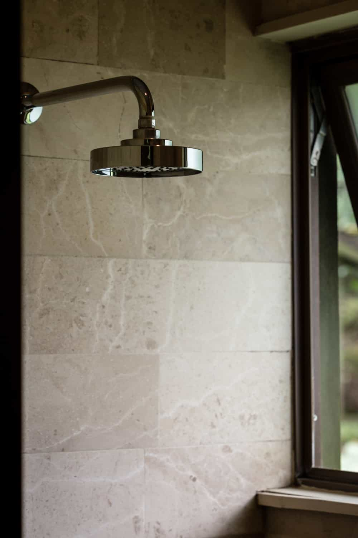 Natural stone shower wall with elegant shower head in honeymoon bathroom.