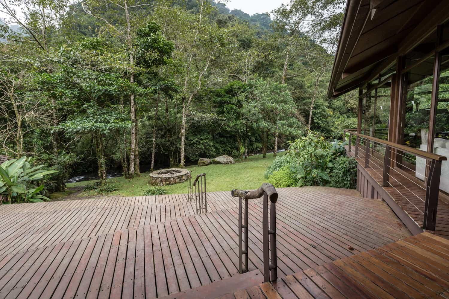 Wedding venue at El Silencio lodge on wood deck with view of cloud forest and river.