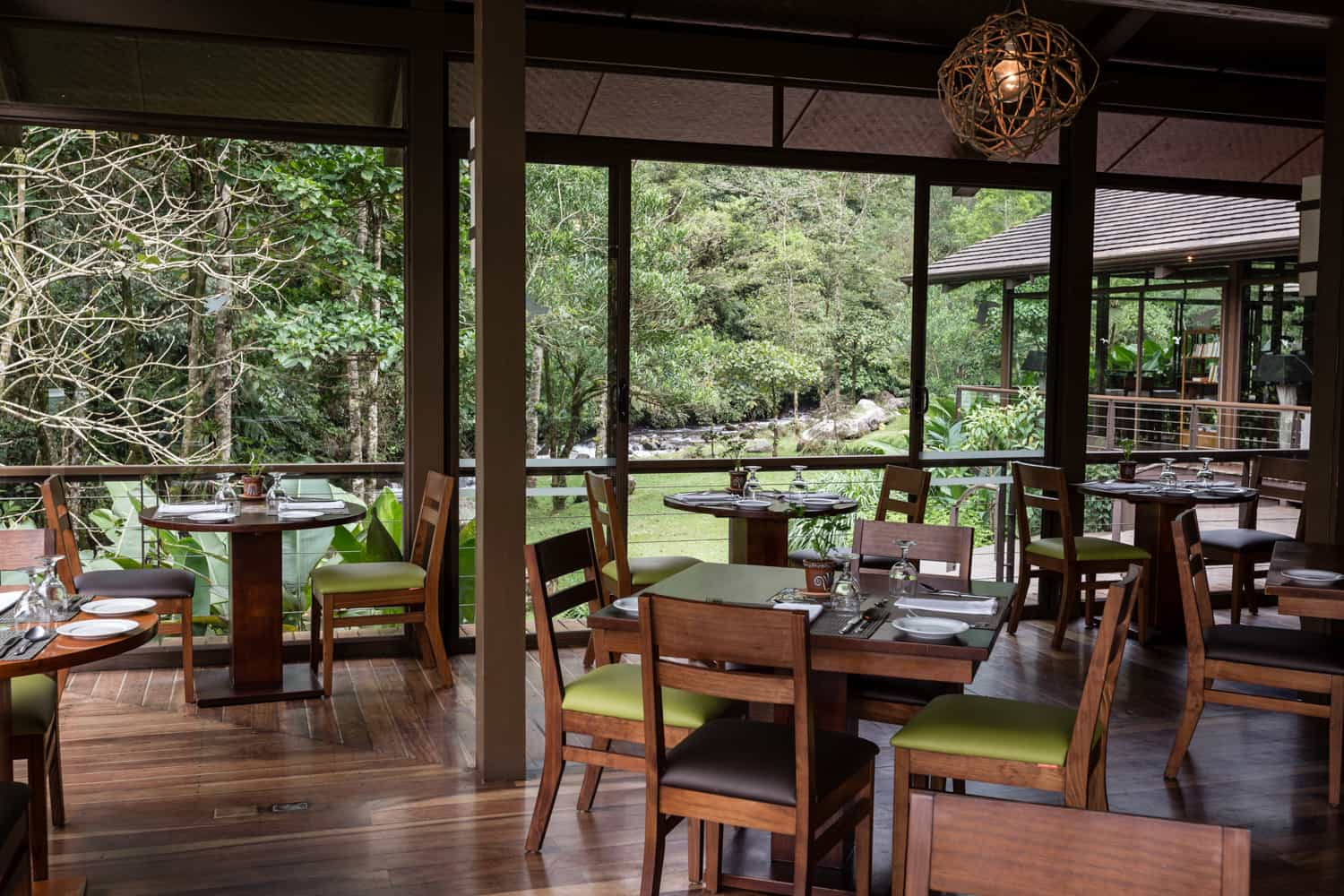 Glass walls in wedding party site with view of river and forest.