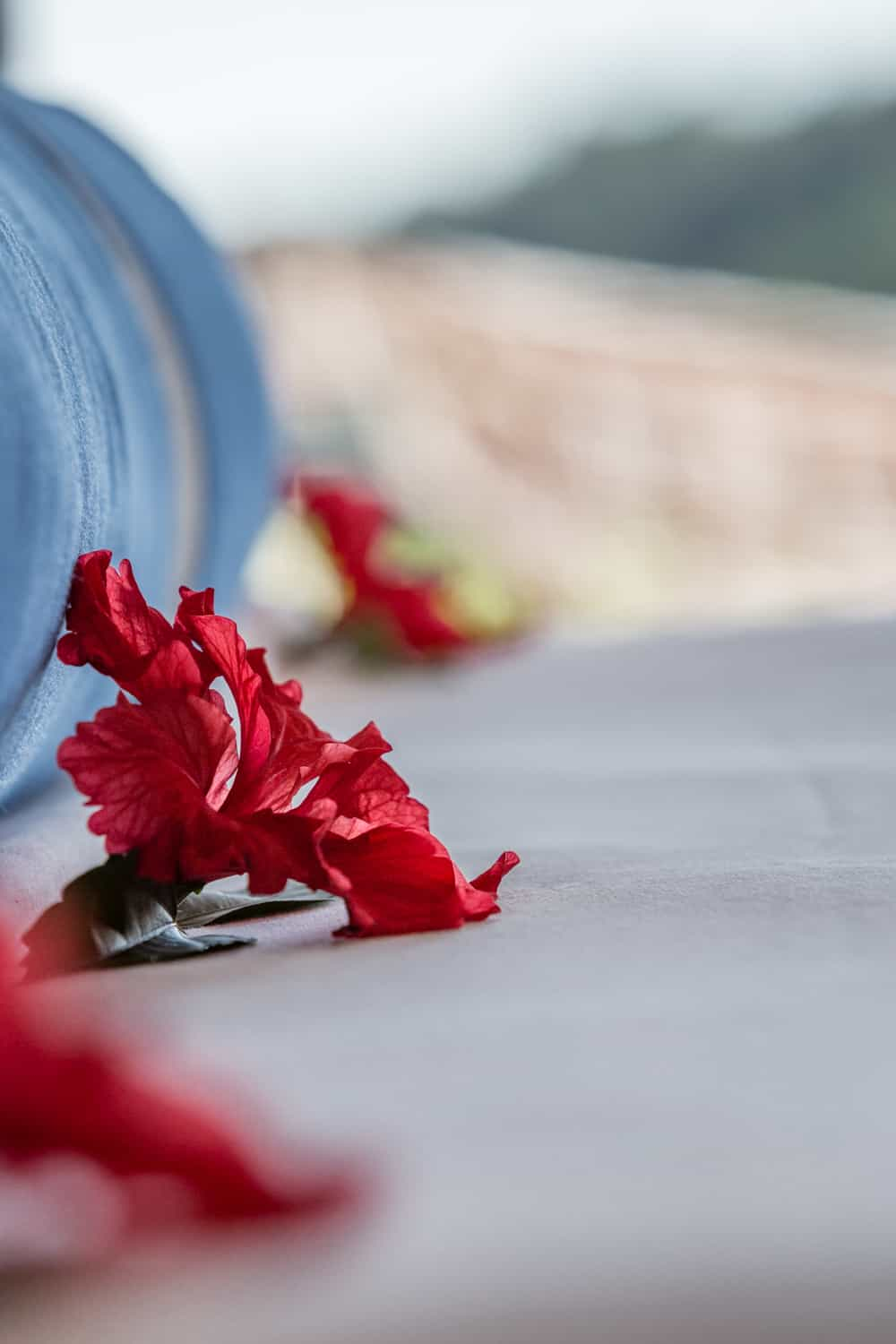 Red flowers on king bed for wedding guests in deluxe accommodations.