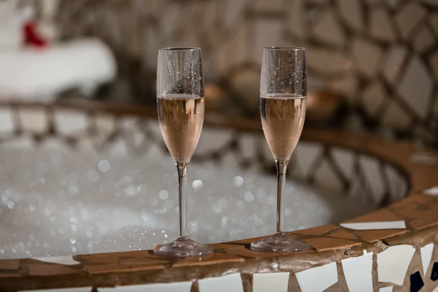 Flutes of champaign by romantic hot tub await couple about to tie the know.