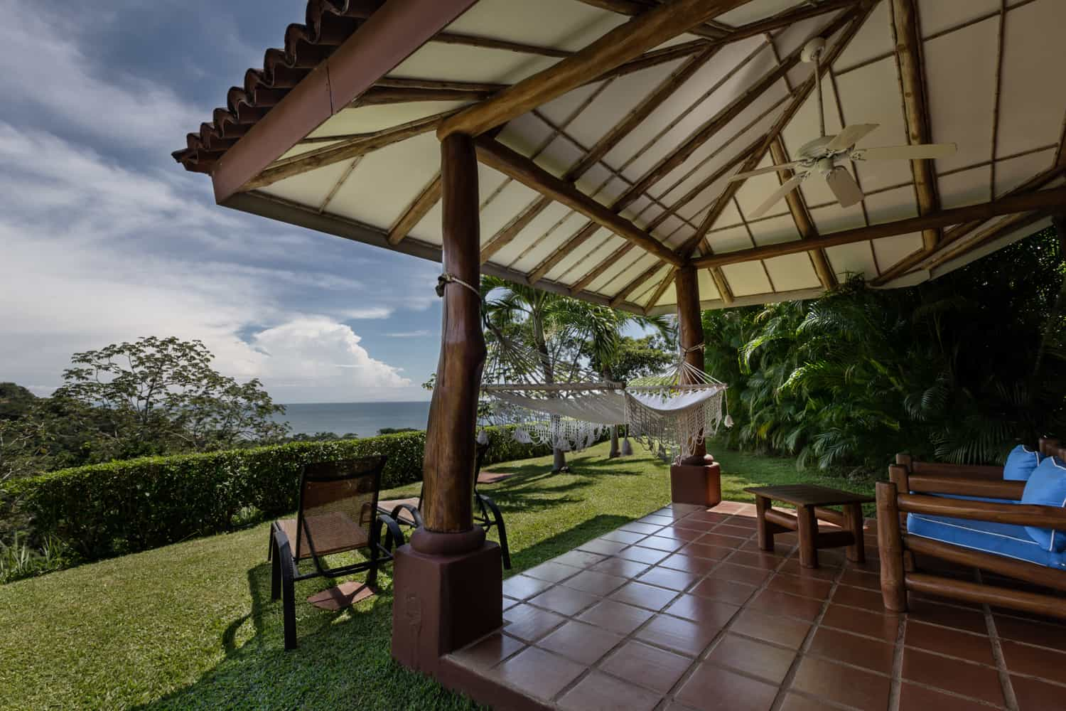 Garden & covered area with view of Pacific Ocean and mountains.