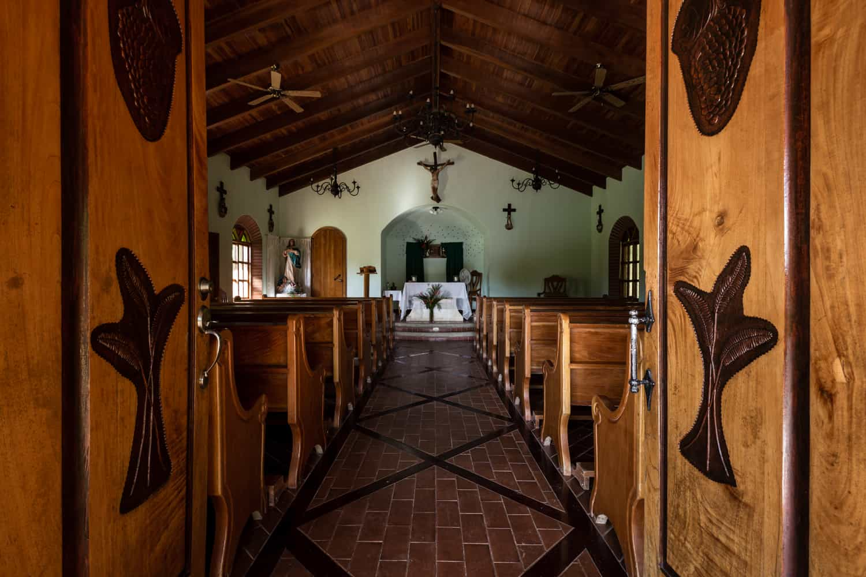 Wood pews line walkway leading to altar.