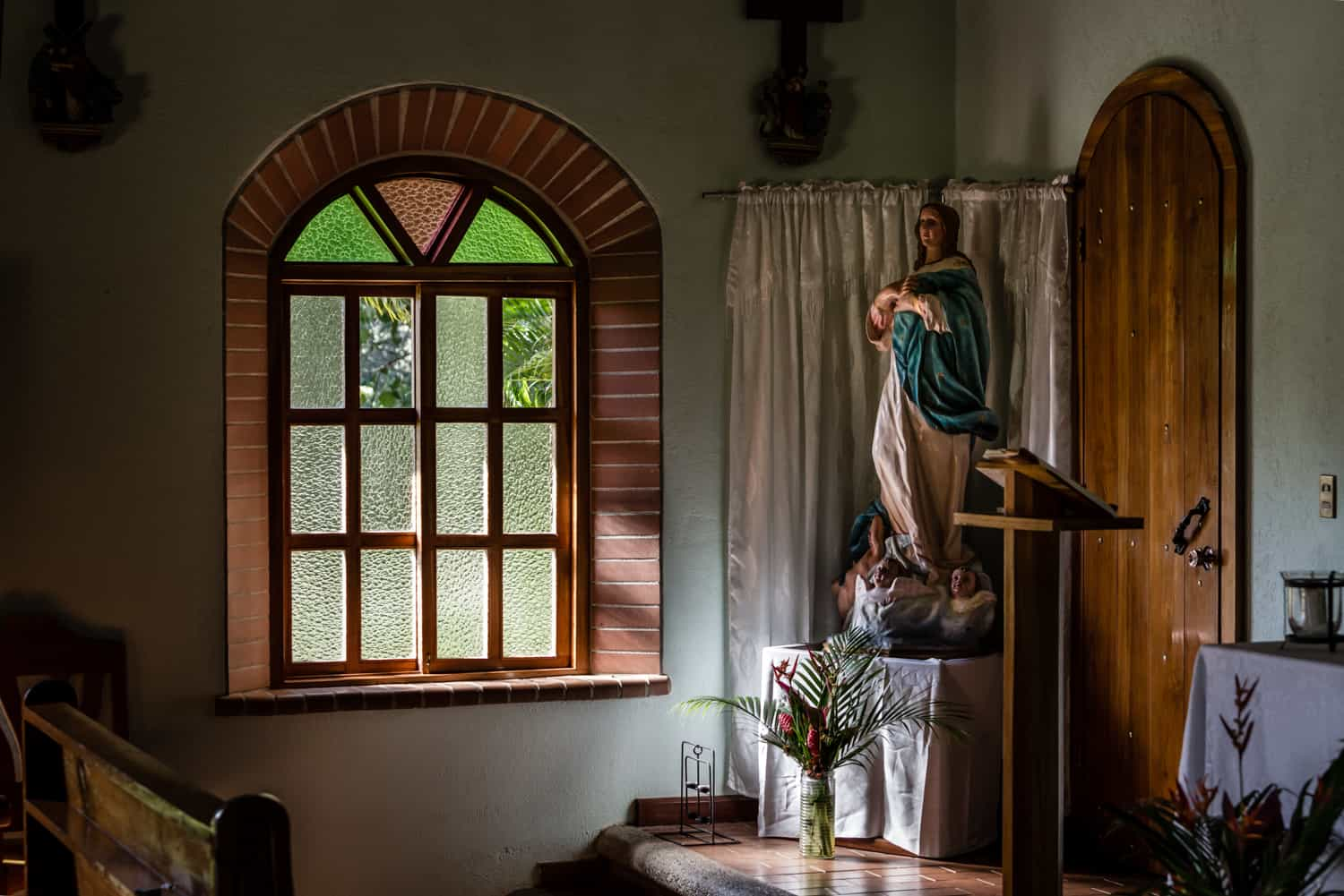 Sunlight pours into church trough window on statue.