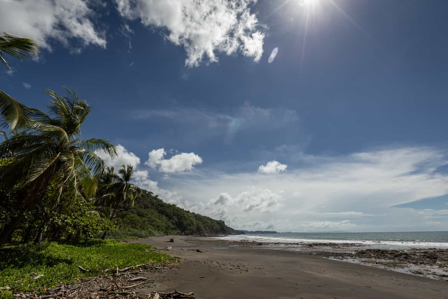 A view of the virgin beach at Hotel Punta Islita stretching in the distance bordered by tropical rainforest.