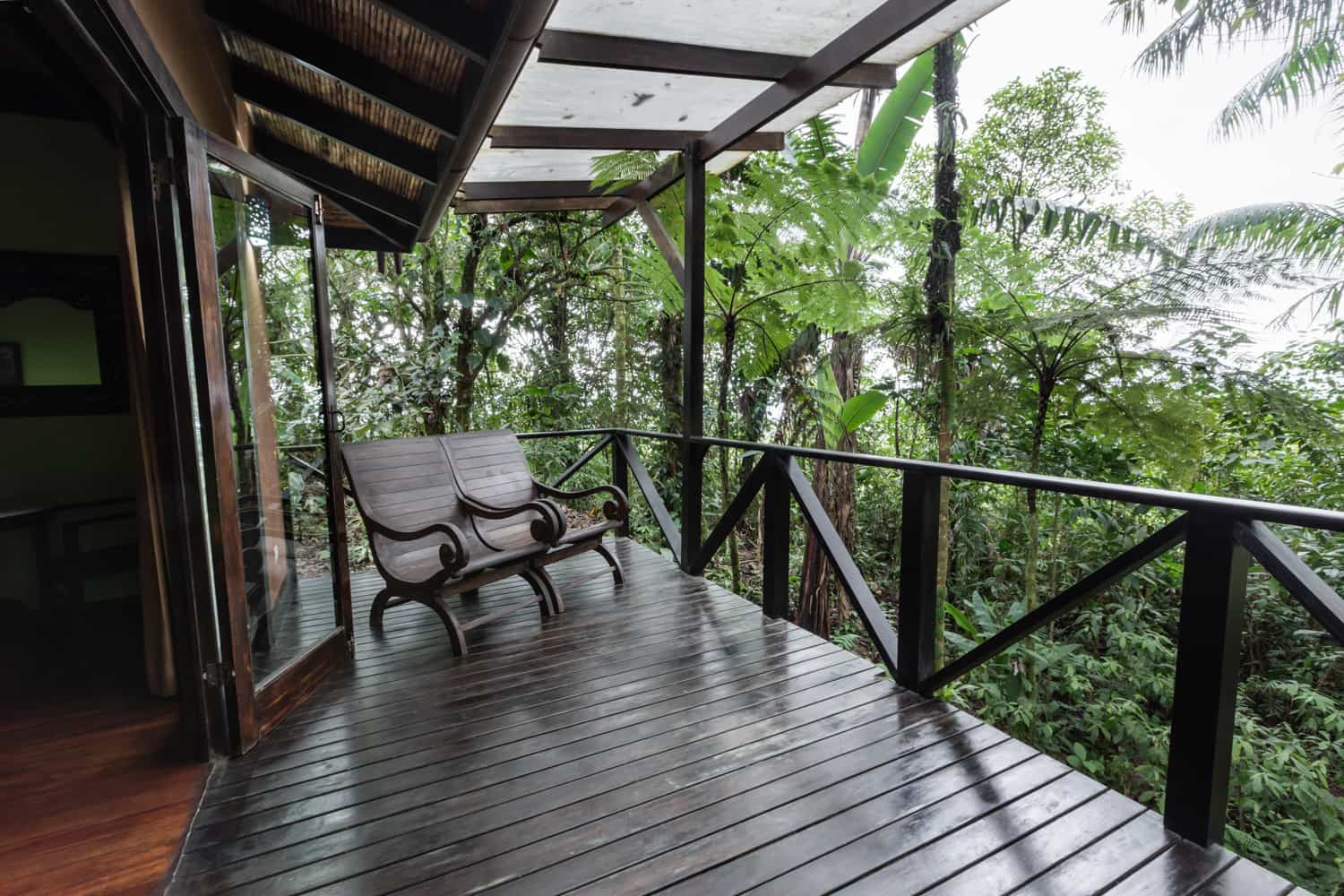 Chairs on wood deck surrounded by rainforest at boutique wedding destination in Costa Rica.