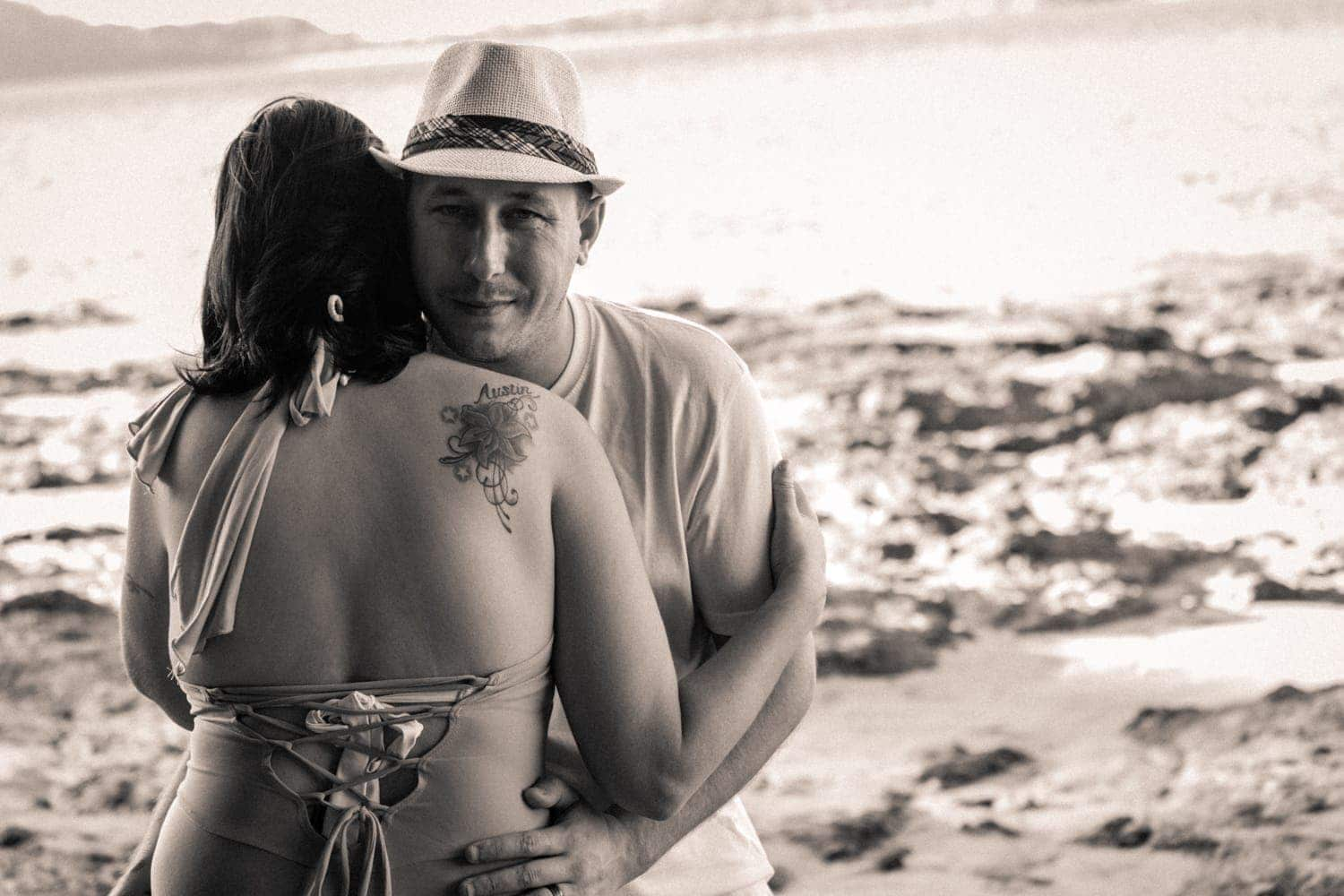 Engagement photo of couple hugging on beach by Arenas Foto.