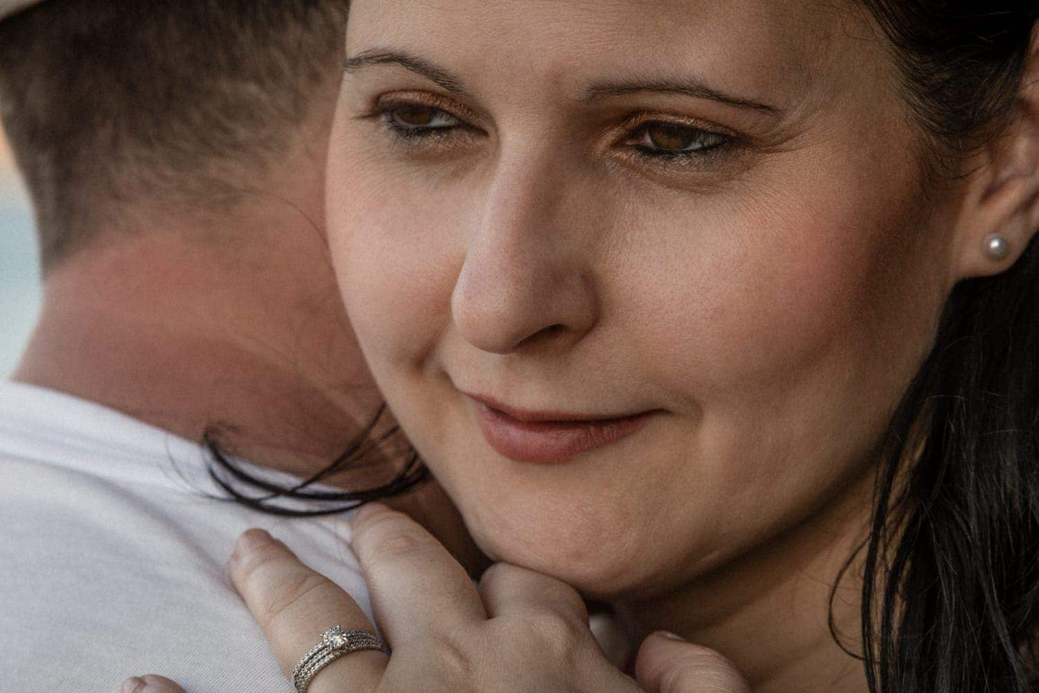 Smiling woman with head on Fiancé's shoulder by Arenas Foto.