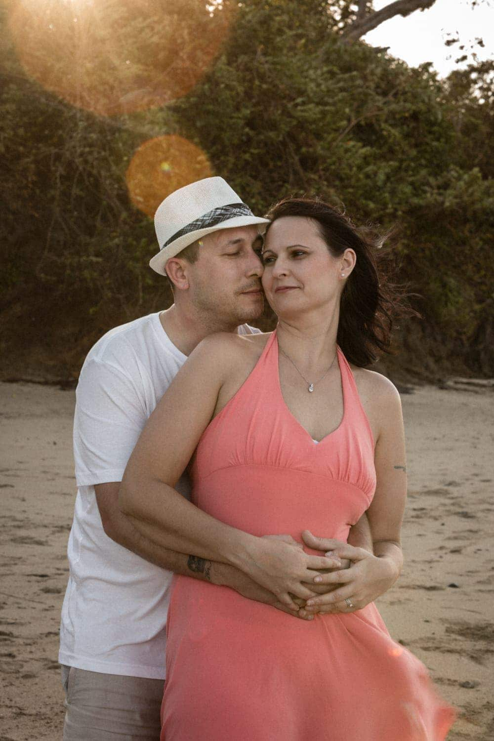 Woman leaning against soon-to-be husband romantically on beach by Arenas Foto.