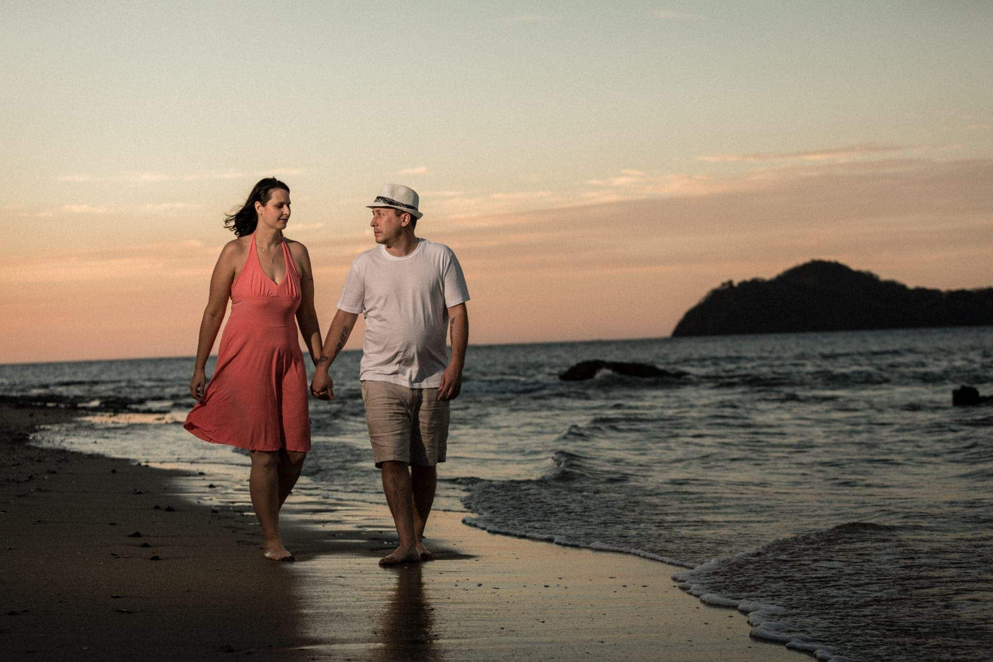 Photo of couple holding hands walking on beach in Costa Rica.