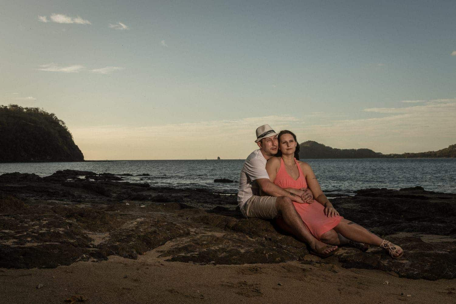 Soon-to-be-married couple pose for romantic beach engagement photo.