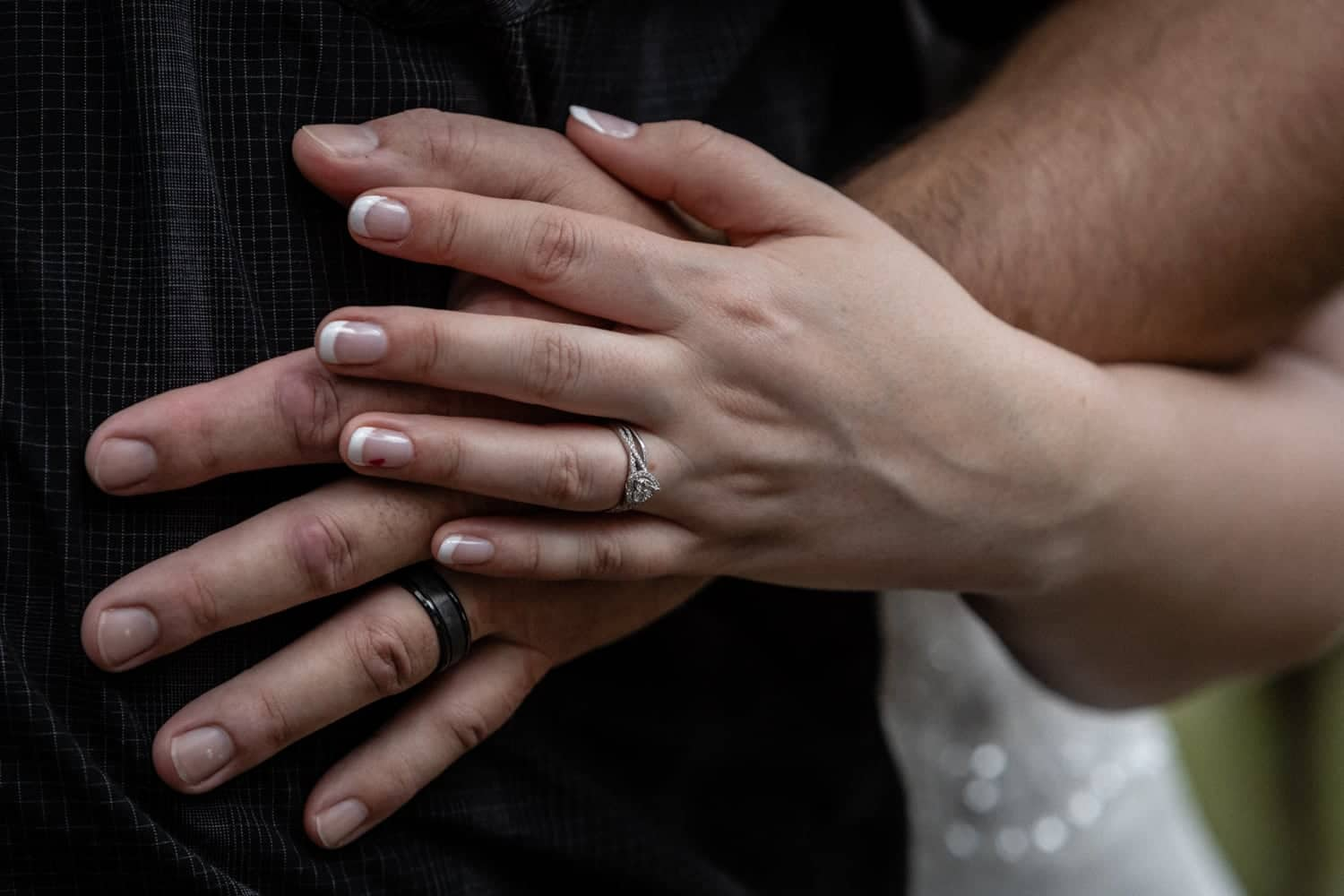 Photo of bride and groom's hands with wedding rings.