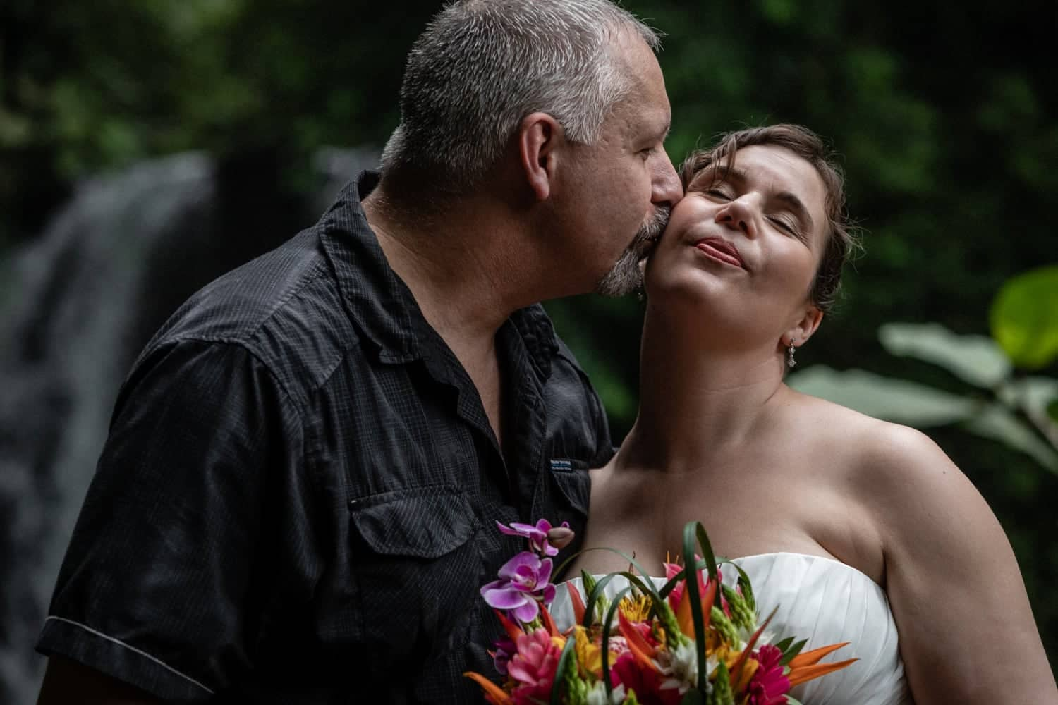 Groom kisses bride's cheek near waterfall after getting hitched in La Fortuna.