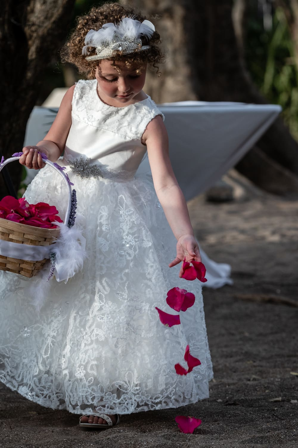 Flower girl in white dress tossing red rose petals on beach sand.