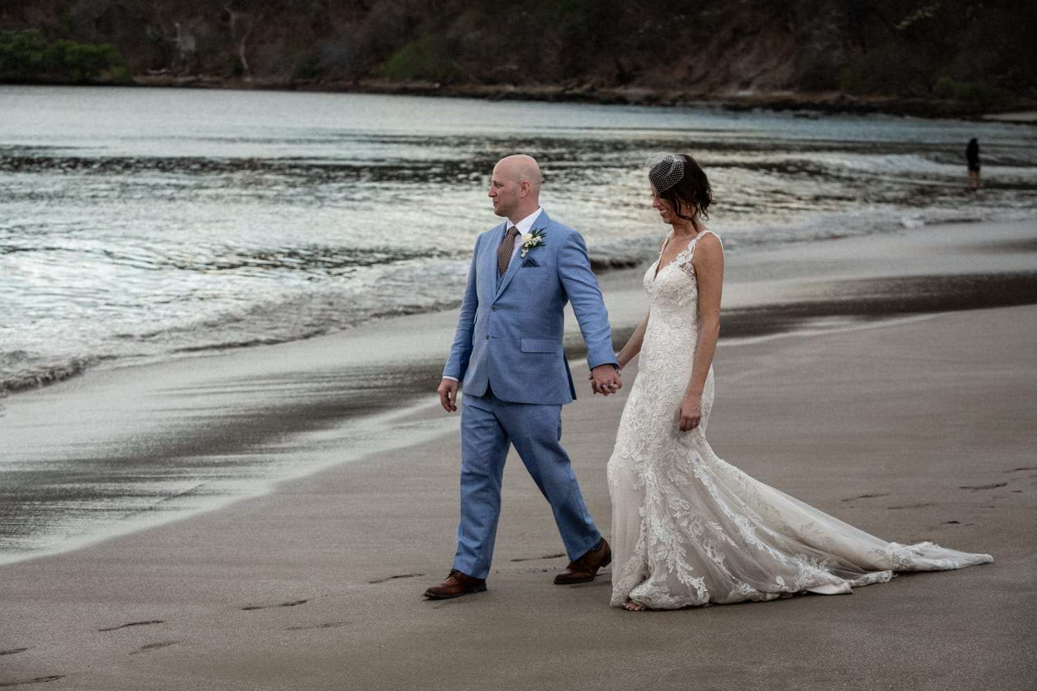Just married couple holding hands walking on beach in Costa Rica.