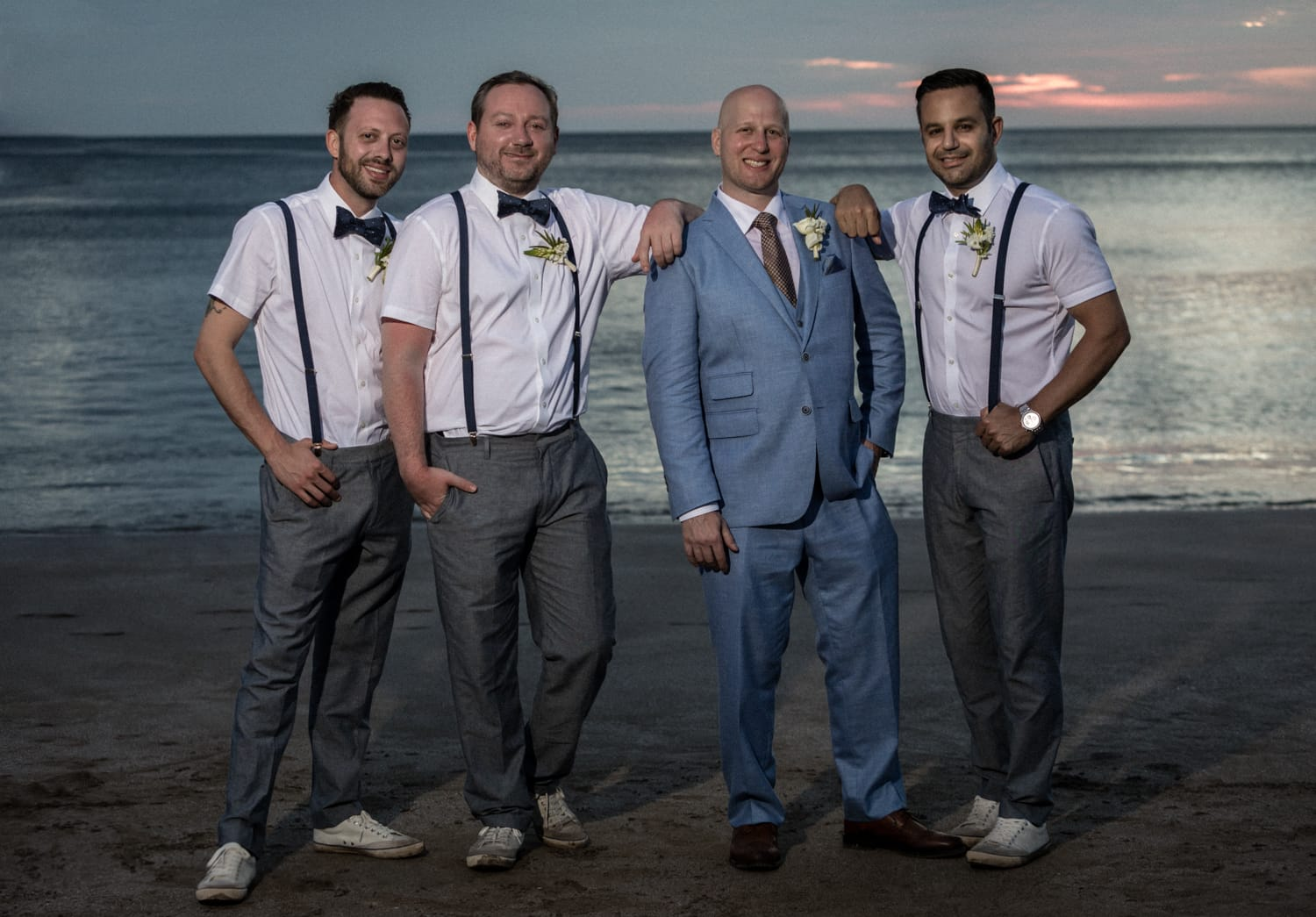 Wedding photo of groom with groomsmen on beach at sunset.