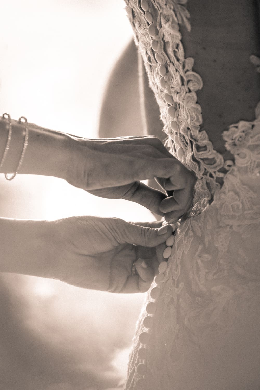 Bridesmaid helps bride put on wedding dress.