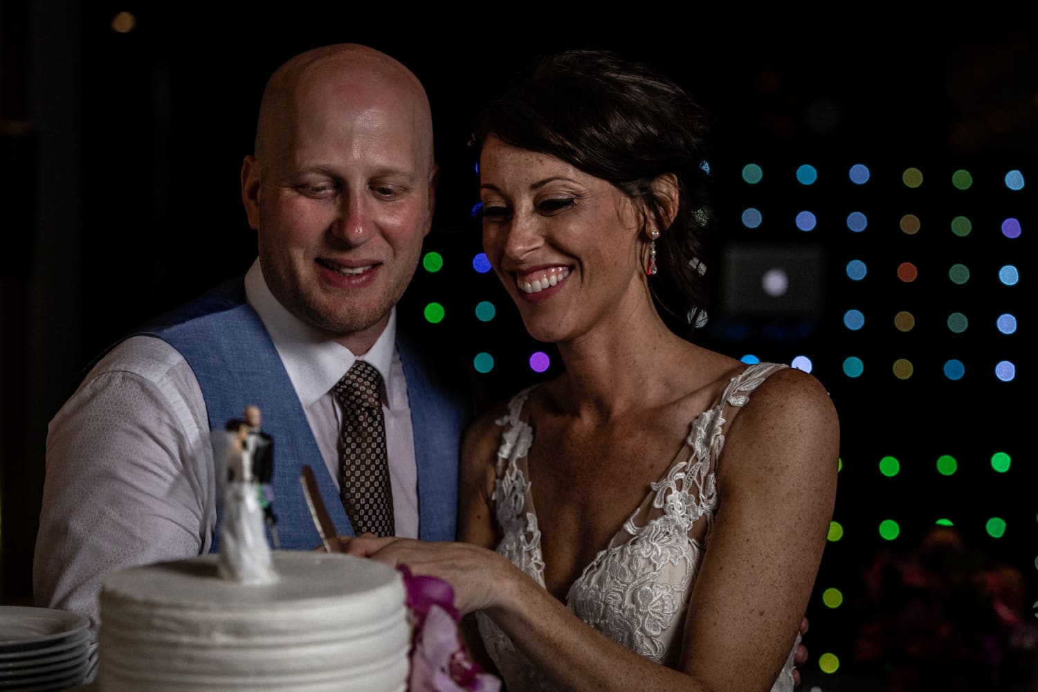 Photo of bride and groom smiling and cutting wedding cake at reception.