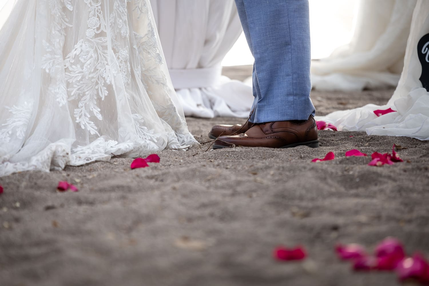 Beach sand aisle with red rose petals.