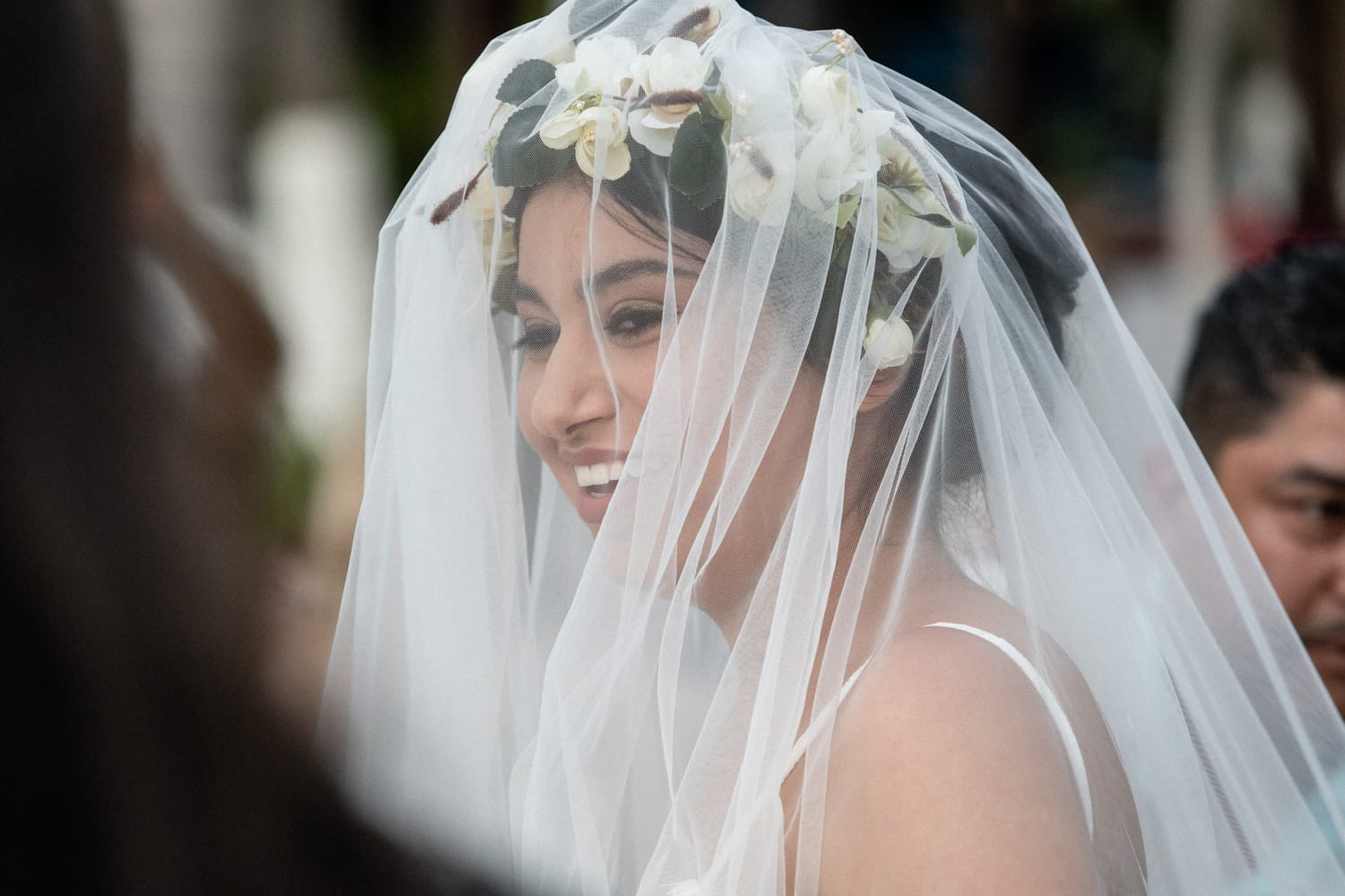 Bride wearing white veil and bridal crown with white flowers.