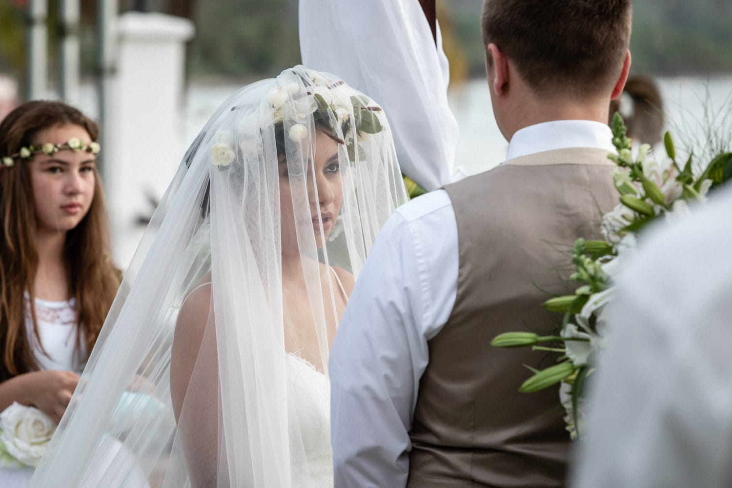 Photo of bride in white veil looking at groom at altar during Costa Rica beach wedding.