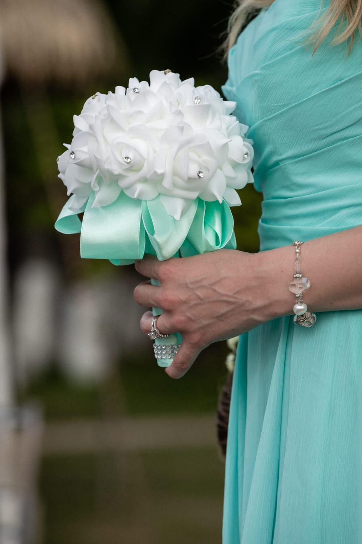 Bridesmaid holds wedding bouquet during beach wedding ceremony.